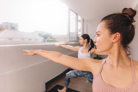 Women doing yoga in warrior pose at studio