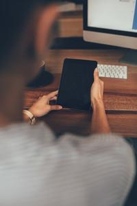 Woman sitting at her desk using digital tablet