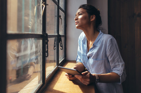 Woman standing by office window with digital tablet