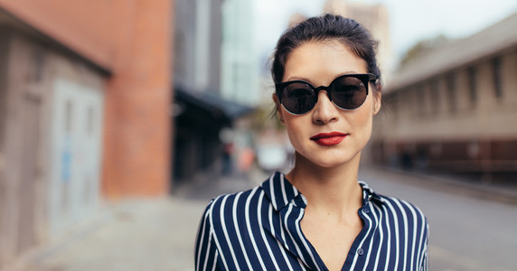 Woman with sunglasses walking outdoors on the city street