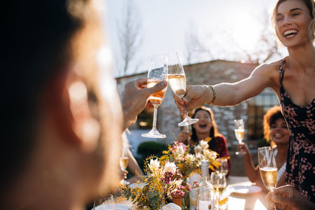 Woman toasting champagne with friend at party