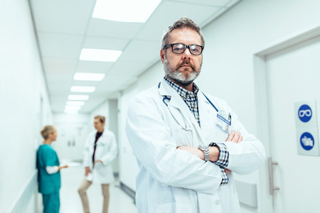 Experienced doctor standing in hospital corridor