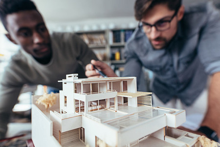 Two architects making architectural model in office