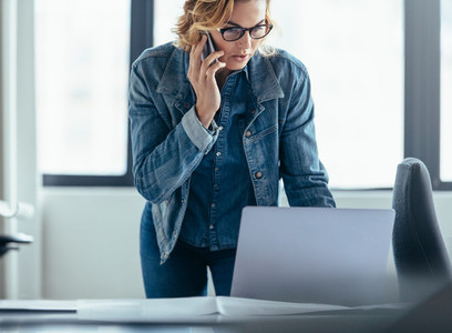 Businesswoman working on laptop and talking on mobile phone