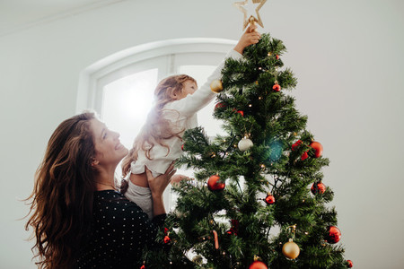 Mother and child decorating Christmas tree