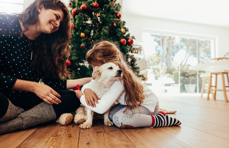 Happy mother and daughter celebrating Christmas with their dog