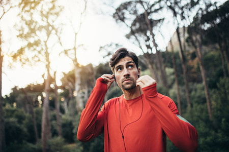 Runner wearing earphones during workout in a park