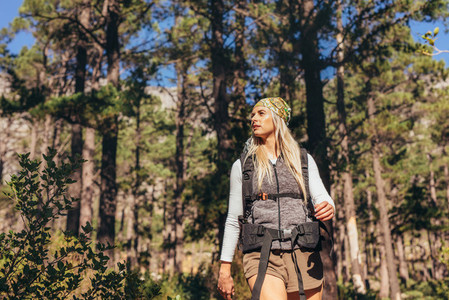 Woman walking in forest wearing a backpack