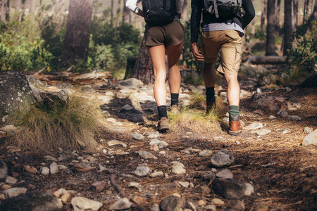 Hiking couple walking on rocks in forest wearing backpacks