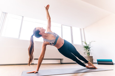 Slim woman doing the side plank yoga pose
