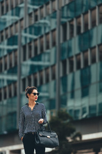 Businesswoman with handbag on the city street