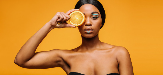Woman with artistic make up holding an orange