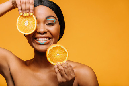 Smiling woman with vivid makeup and orange