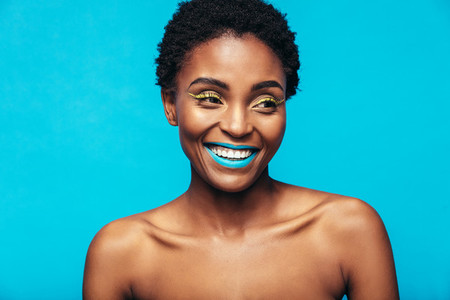 Smiling african woman wearing vivid makeup