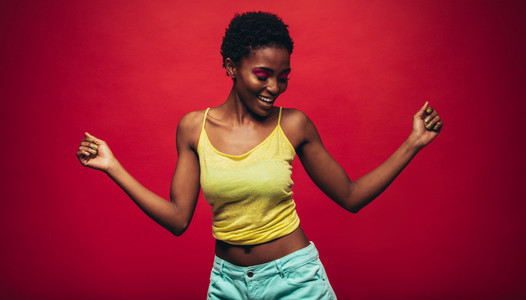 African woman dancing over red background