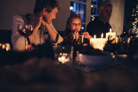 Cute little girl sitting with family for christmas dinner