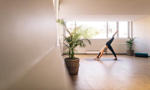 Fitness woman practising yoga indoors