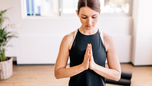 Young woman in namaste yoga pose