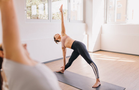 Woman doing triangle pose in yoga class