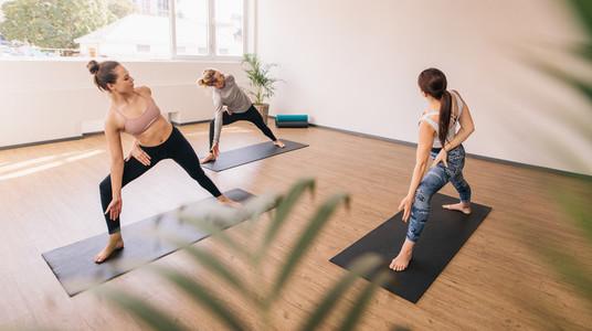 Three people practising yoga in class
