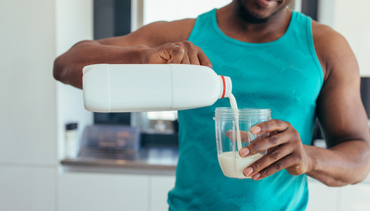 Man pouring milk in glass for breakfast