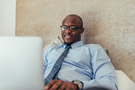 Businessman working on laptop computer sitting on bed