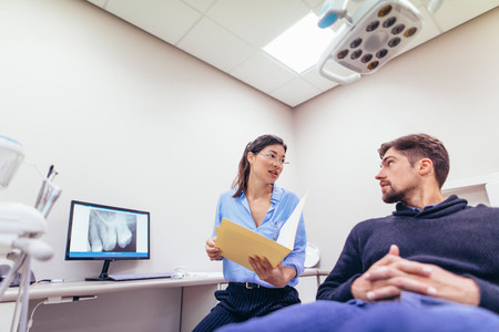 Dentist discussing report with patient at dental clinic