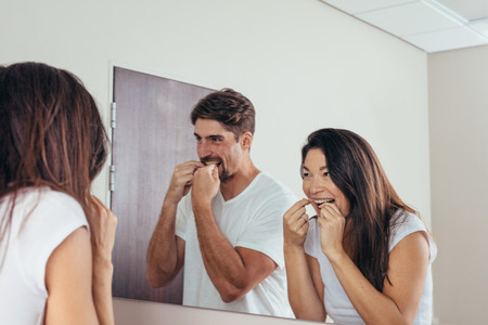Couple using dental floss to clean their teeth