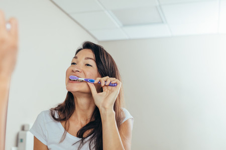 Woman brushing teeth in the bathroom