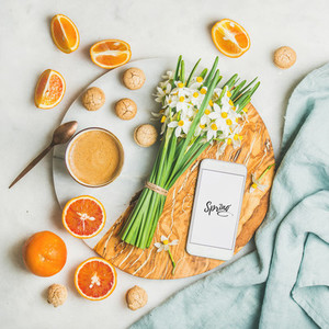 Coffee cookies oranges flowers and mobile phone with word Spring