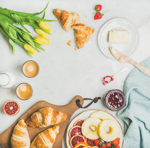 Breakfast table with coffee milk pasrties jam and yellow tulips