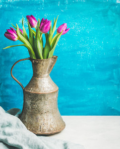 Spring purple tulips in vintage rustic copper jug blue background