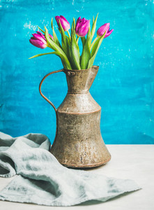 Spring purple tulips in vintage rustic copper jug blue wall