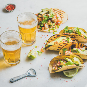 Healthy corn tortillas with beer in glasses over light background