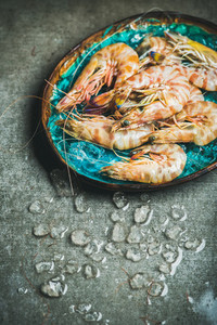 Raw uncooked tiger prawns on chipped ice in tray