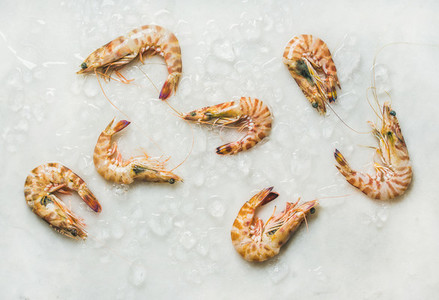 Raw tiger prawns on chipped ice over light grey background