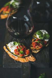 Brushetta with eggplant  tomatoes  garlic  cream cheese  arugula  glass of wine