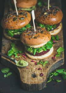 Healthy homemade vegan burger with beetroot quinoa patty and avocado sauce