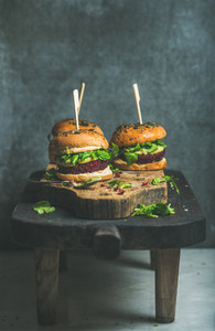 Healthy vegan burger with beetroot quinoa patty and arugula on table