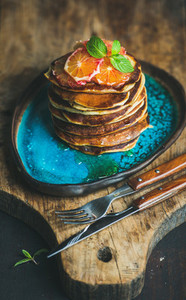Homemade pancakes with honey bloody orange slices and mint leaves