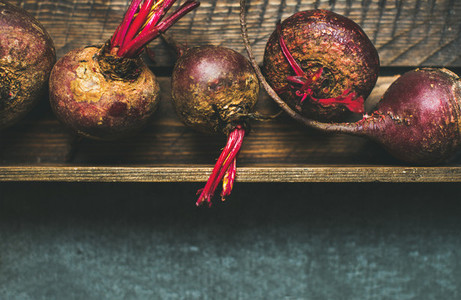 Raw organic purple beetroots in wooden box copy space