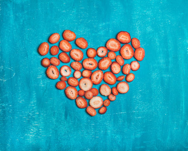 Pieces of fresh strawberry placed in heart shape  blue background