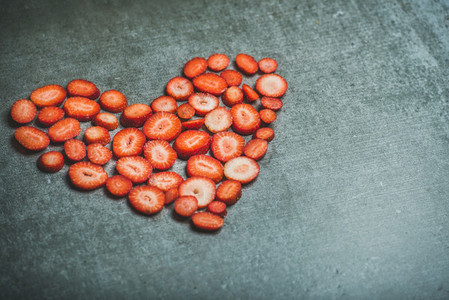 Heart shaped pieces of strawberries over grey concrete background