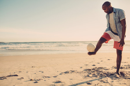 Man playing with football along the beach