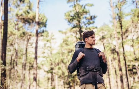 Man hiking in forest wearing a backpack