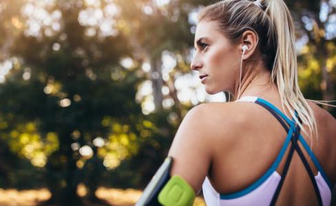 Woman runner wearing earphones during workout