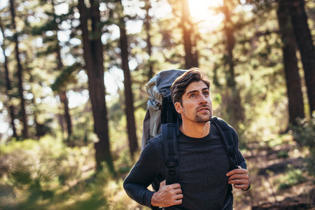 Man walking in forest wearing a backpack