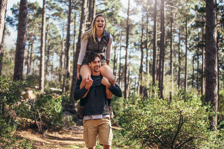 Man carrying his woman partner on his shoulders while trekking i