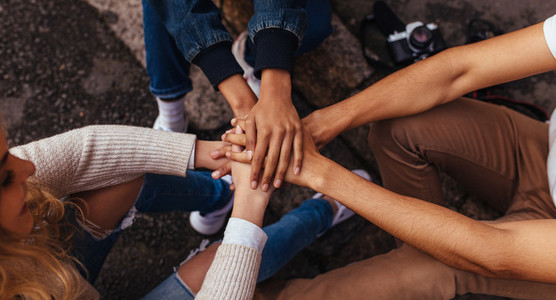 Group of friends sitting together stacking their hands on one an
