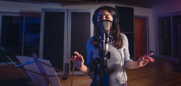 Female singer singing a song in recording studio